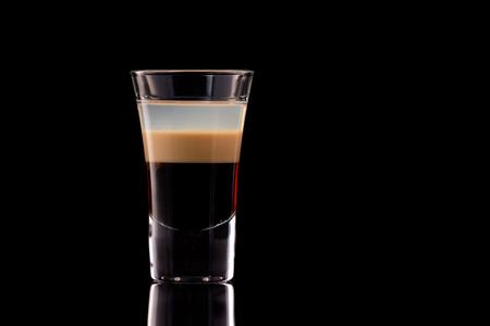 B 52 alcohol layered shooter cocktail isolated at black background. Standard-Bild - 111416253