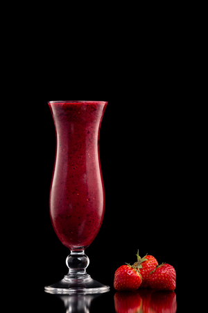 Glass of red currant berries fresh shake decorated with strawberries isolated at black background.