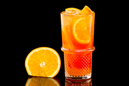 Closeup glass of fresh orange juice with ice isolated at black background.