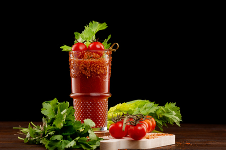 Glass of bloody mary cocktail decorated with celery and pepper and a branch of red tomatoes on a wooden table isolated at black background. Stock Photo