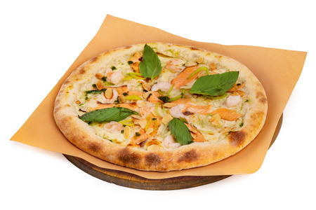 Tasty italian pizza with salmon, seafood and basil on a paper at wooden board isolated at white background.