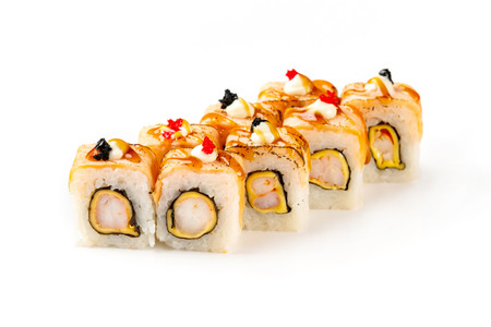Japanese sushi rolls with crab, shrimps and cream cheese decorated with masago caviar and teriyaki sauce isolated at white background. Imagens