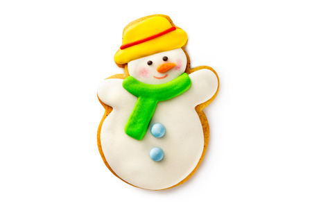 Closeup gingerbread christmas snowman wearing yellow hat and green scarf cookie isolated at white background. Stockfoto