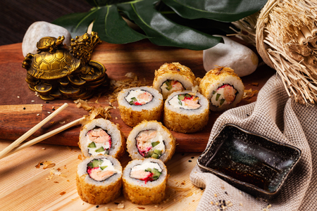 Closeup set of hot tempura sushi rolls with tuna, cheese, cucumber and tobico at wooden board at decorated with sackcloth and green plant table background.