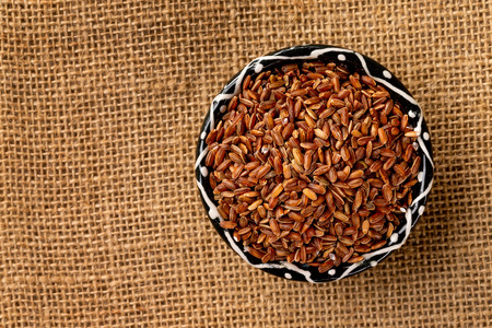 Top view bowl of red rice at sackcloth background arranged at right side.