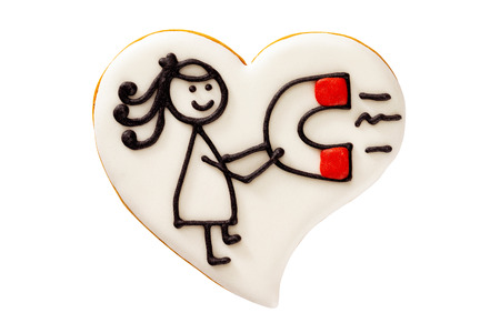 Closeup gingerbread heart cookie with a drawing of a girl with magnet isolated at white background. Concept for Valentines day holiday.