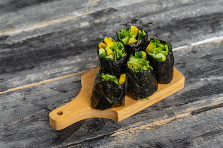 Set of healthy vegetarian vegetables sushi rolls with cucumber, pepper and green salad at wooden table background. Reklamní fotografie