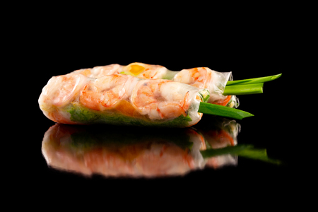Closeup image of goi cuon spring rolls with shrimps, onion, mango, pork and noodles isolated at black background. Traditional vietnamese food.