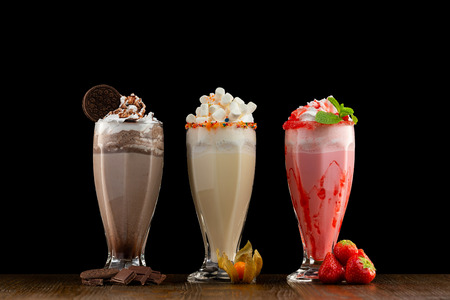 Three glasses of colorful milkshake cocktails - chocolate, strawberry and vanilla decorated with fresh berries and mint isolated at wooden table background.