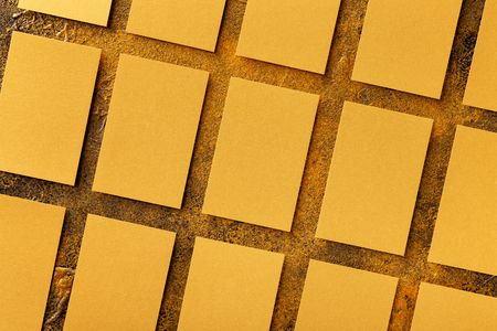 Mockup of blank golden foil business cards stacks arranged in rows at textured golden background. Top view