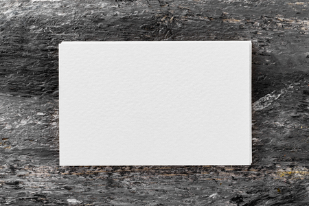 Mockup of white blank business card stack at wooden vintage table background.