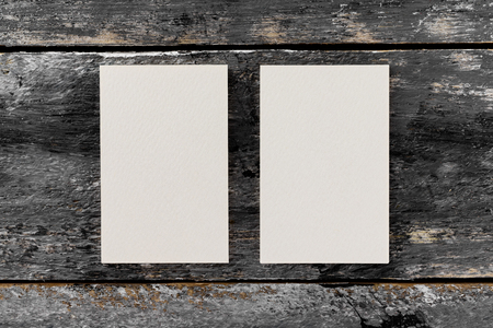Mockup of two white vertical blank business cards at wooden vintage table background.