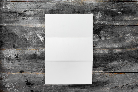 Top view mockup of white opened three fold blank brochure at wooden vintage table background.