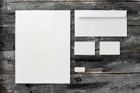 Corporate stationery set mockup at wooden table background. Blank white textured brand ID elements. Imagens