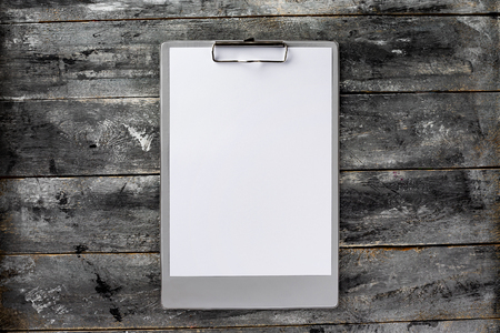 Top view mockup of clipboard and white blank letterhead at wooden vintage table background.