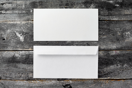 Top view mockup of white blank envelope and brochure at wooden table background.