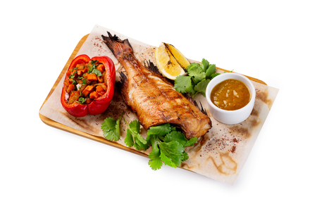 Grilled fish with no head served on paper at wooden board with parsley, pepper, lemon and sauce isolated at white background. Imagens