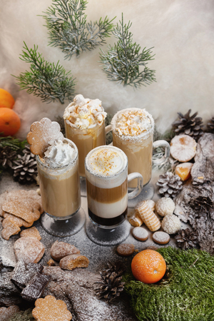 Vertical image of layered christmas coffee glasses set at decorated with moss, tangerines, cookies, sugar powder as a snow natural wooden board bakground.