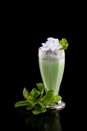 Glass of milk shake cocktail with fresh green mint isolated at black background.