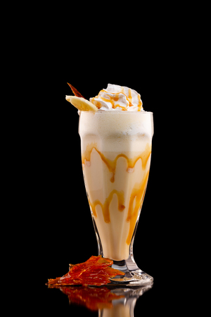 Closeup glass of caramel milk shake isolated at black background.