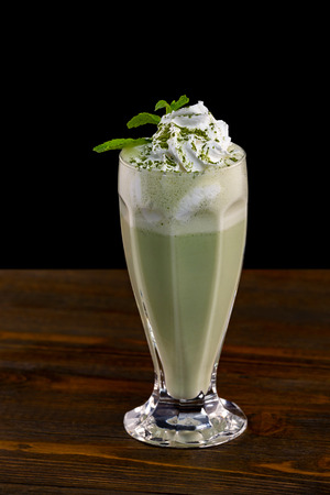 Closeup glass of mint milk shake decorated with whipped cream isolated at black background. Imagens