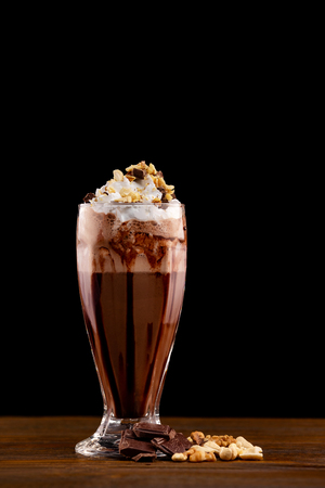 Closeup glass of chocolate milk shake with nuts decorated with whipped cream isolated at wooden board background. Imagens