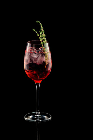 Glass of red sangria wine cocktail decorated with thyme isolated at black background.