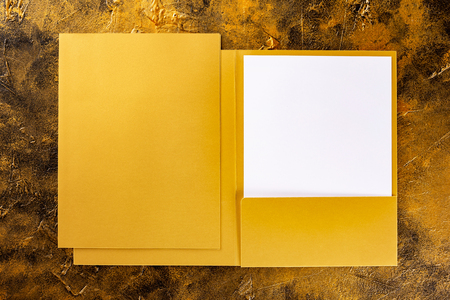 Corporate stationery set mockup. Golden foil opened and closed presentation folders and letterhead at golden textured background.