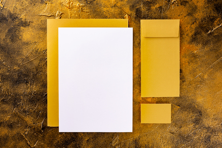 Brand identity mockup. Blank golden foil corporate stationery set of letterhead, closed presentation folder, business card and envelope at golden textured background.