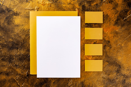 Brand identity mockup. Blank golden foil corporate stationery set of letterhead, closed presentation folder and four business cardsat golden textured background.