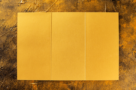 Top view mockup of opened three fold golden foil brochure isolated at golden textured background.