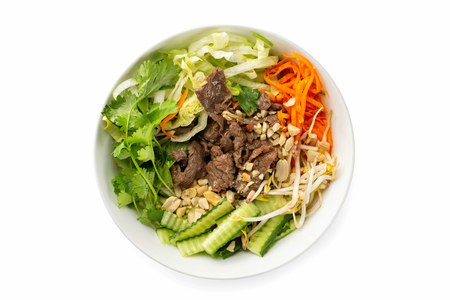 Closeup vietnamese healthy fresh salad of beef meat, bamboo, cabbage, cucumber and carrot served in a bowl isolated at white background.