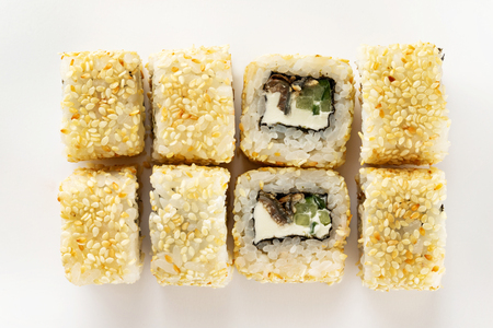 Closeup top view set of sushi rolls with sesame, eel and cucumber isolated at white background.