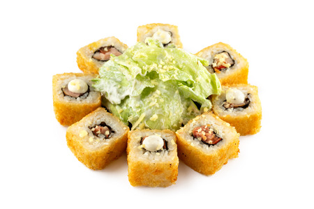 Closeup hot set of sushi rolls with eel, cheese served with green salad and sauce isolated at white background.