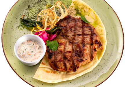 Grilled pork steak served on a plate with lavash, vegetables and sauce isolated at white background.