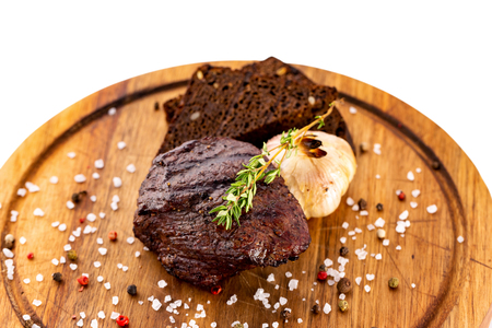 Filet mignon steak served with garlic at a wooden board isolated at white background.