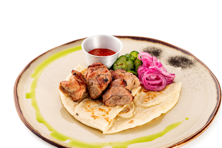 Plate with pork meat shashlik - traditional barbecue meal served with lavash, vegetables and ketchup isolated at white background. Imagens