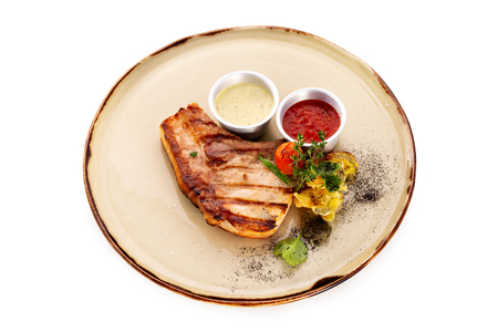 Grilled pork steak served on a plate with vegetables and sauce isolated at white background.