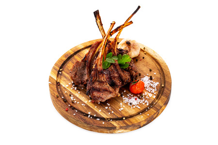 Grilled lamb racks served witth salt and garlic at a wooden board isolated at white background.