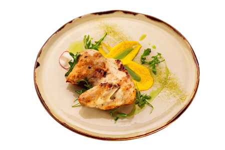 Grilled chicken breast served with sauce on a plate isolated at white background.