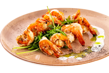 Plate of grilled shrimps served with sauce isolated at white background.