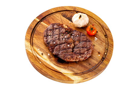 Ribeye steak served with tomato and garlic at a wooden board isolated at white background. Imagens