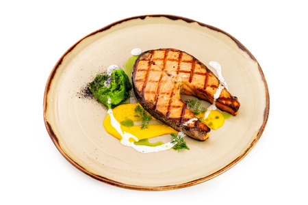 Plate of grilled salmon fish steak served with cream sauce isolated at white background.