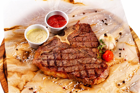 T bone fresh juicy steak served with ketchup and sauce at a wooden board isolated at white background.