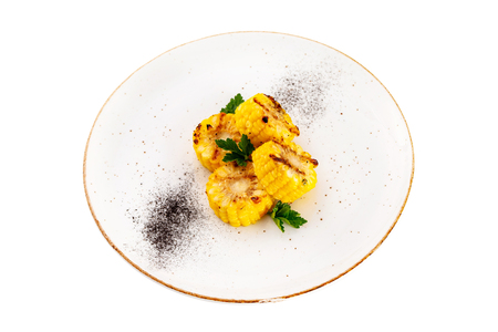 Plate of grilled golden sweet corn served with green and pepper isolated at white background.