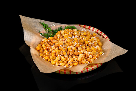 Fried corn snack served on paper at a plate isolated at black background.