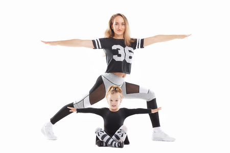 Portrait of healthy family of mother standing in fitness pose above little daughter and making exrecises isolated at white background. Imagens