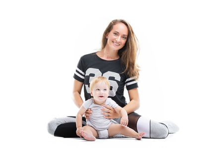 Smiling mother is sitting with happy child at white iosolated background. Concept of happy family.