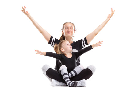 Portrait of healthy family of mother sitting in yoga pose with little daughter and raising hands isolated at white background. Imagens