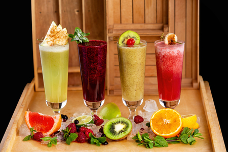 Group of fresh healthy fruit smoothies at wooden table background with ingredients around.